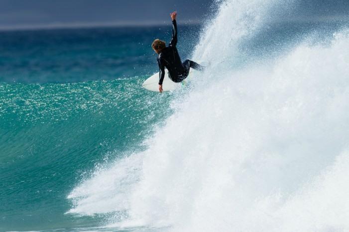 Surfero cogiendo una ola en Jeffrey's Bay, Sudáfrica.
