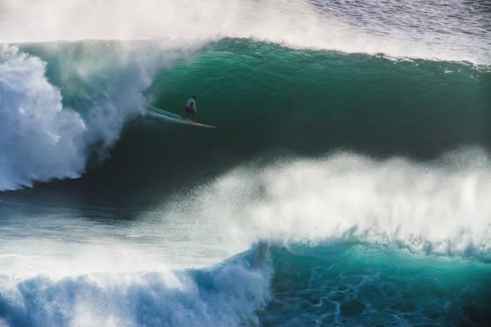 Surfero cogiendo una de las peligrosas olas de Mavericks, California.