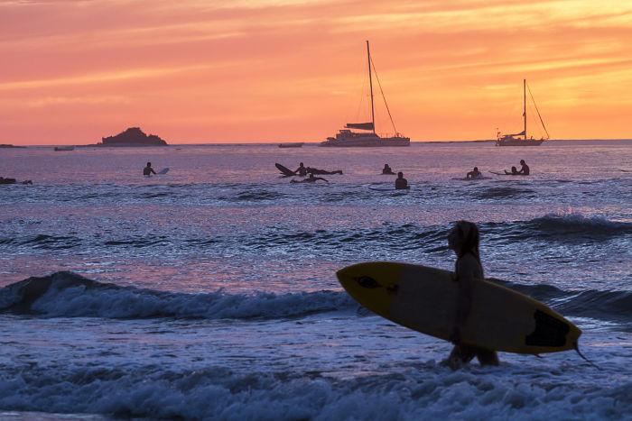 Surf al atardecer en la playa de Tamarindo, Costa Rica.