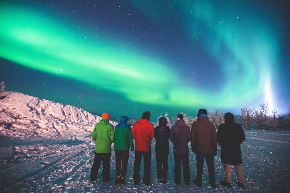 Amigos contemplando una aurora boreal