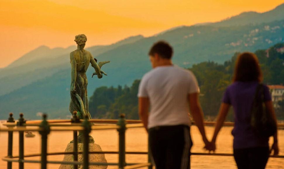Pareja paseando frente a la famosa estatua