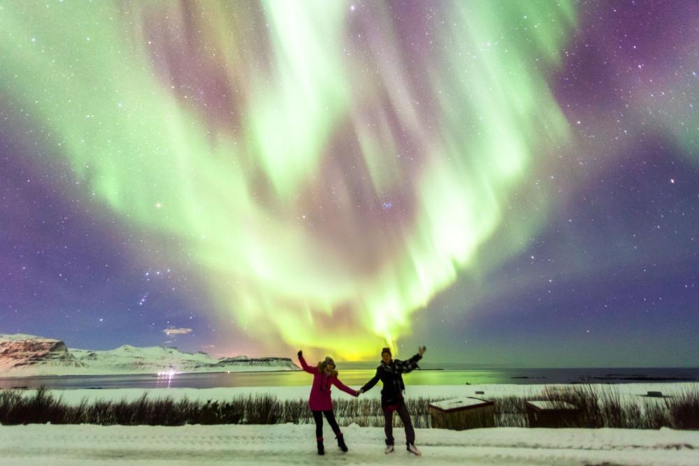 Pareja contemplando una aurora boreal en Islandia