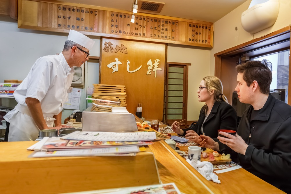 Turistas comiendo sushi en un restaurante de Tokyo