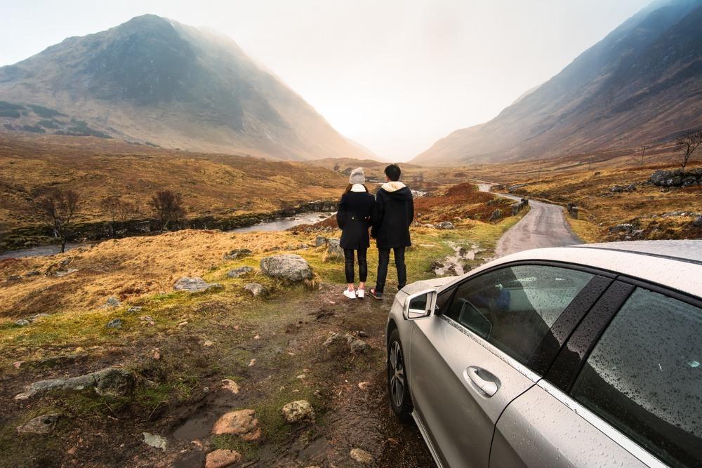 Pareja de ruta en coche por Escocia