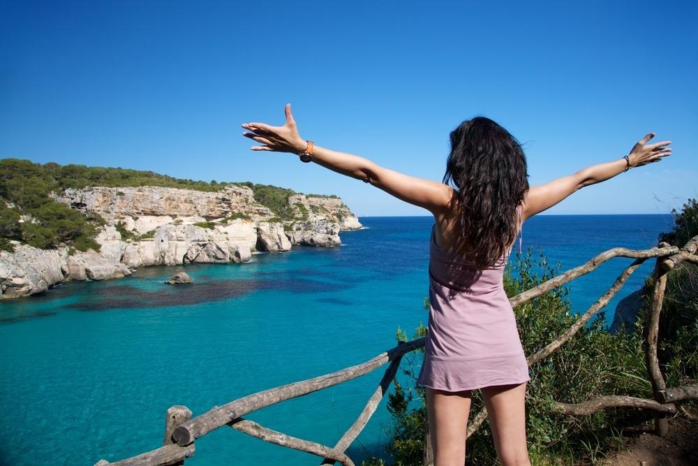 Chica disfrutando de una playa en Menorca