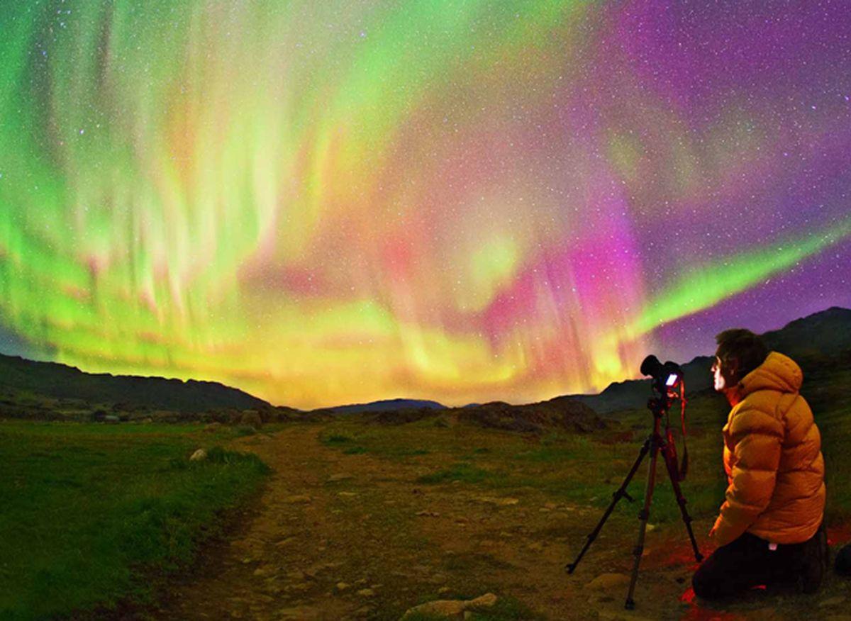 Chico fotografiando aurora boreal en Utsjoki