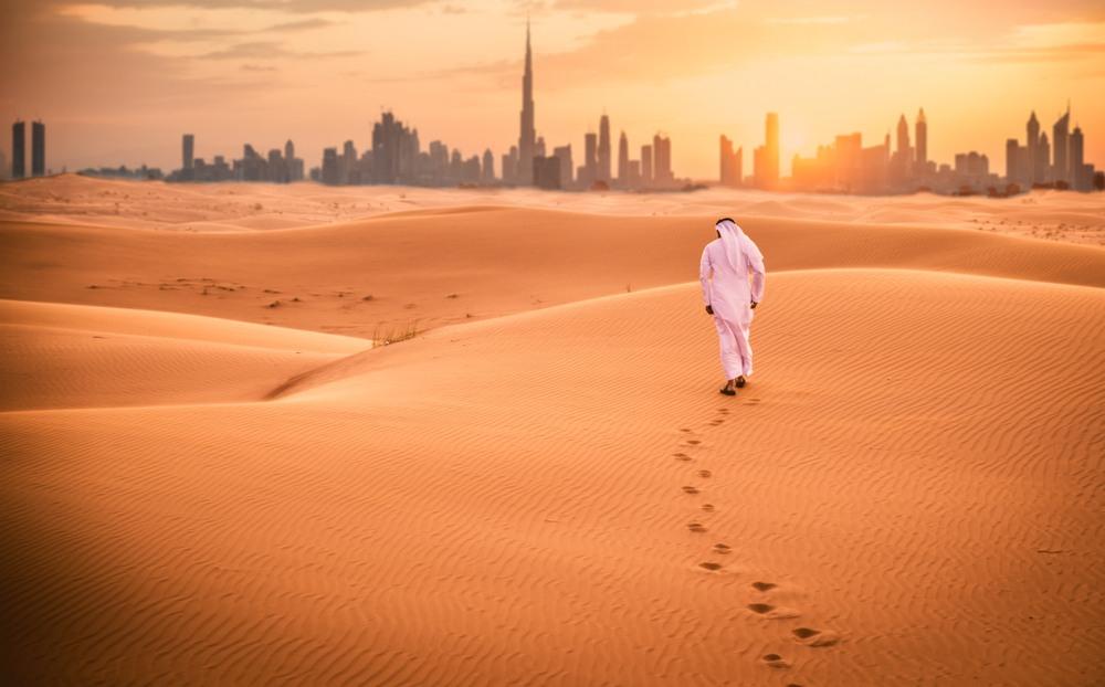Hombre árabe con la vestimenta tradicional caminando en el desierto de Dubái