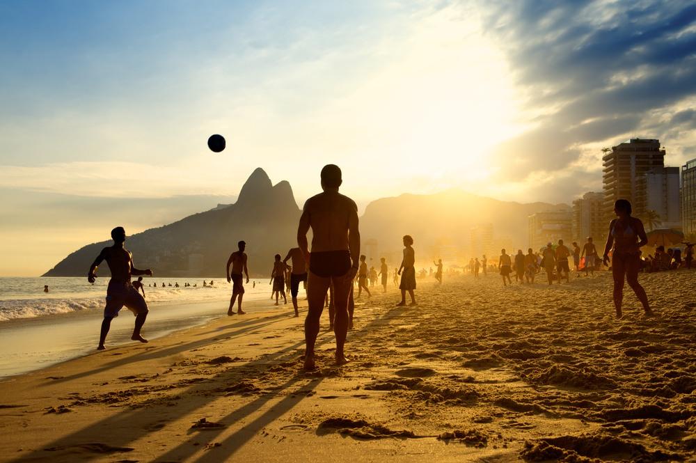 Grupo de jóvenes disfrutando del atardecer en la playa de Ipanema Beach en Rio de Janeiro